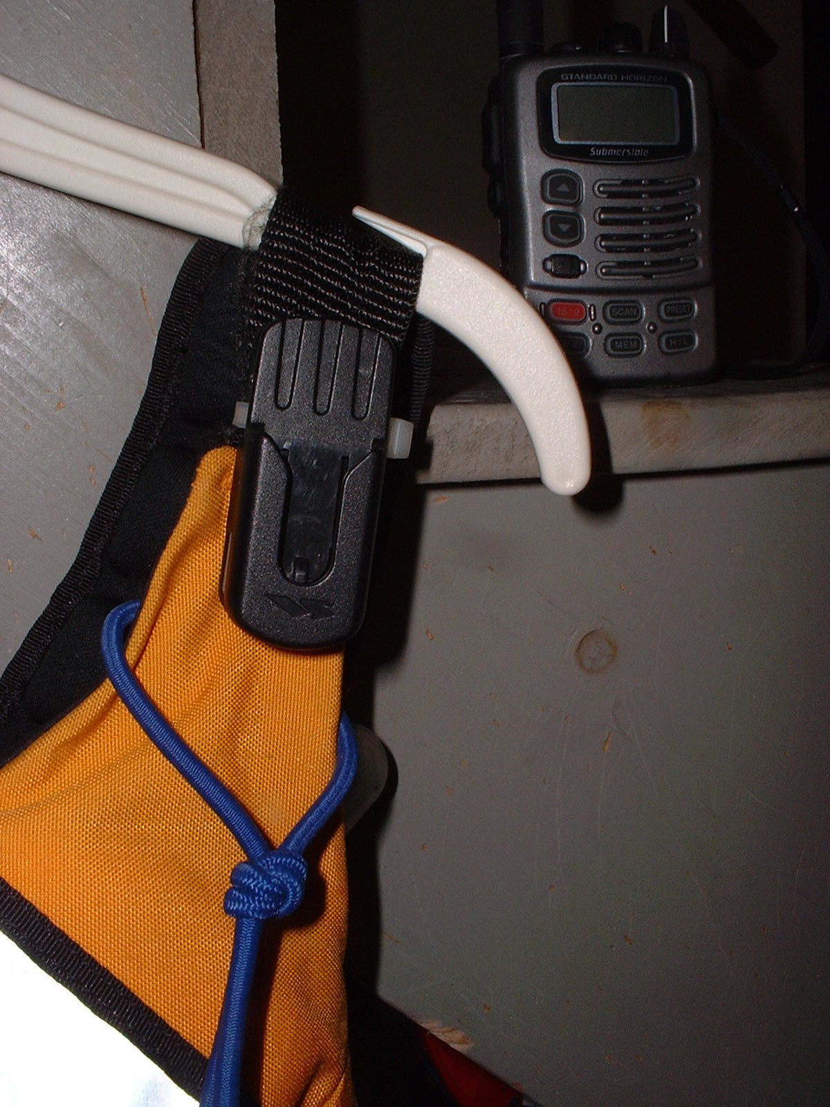 VHF radio belt clip mounted to a PFD shoulder strap