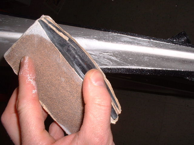 Using a flat and curved sanding block to remove damage gelcoat and feather the edges.