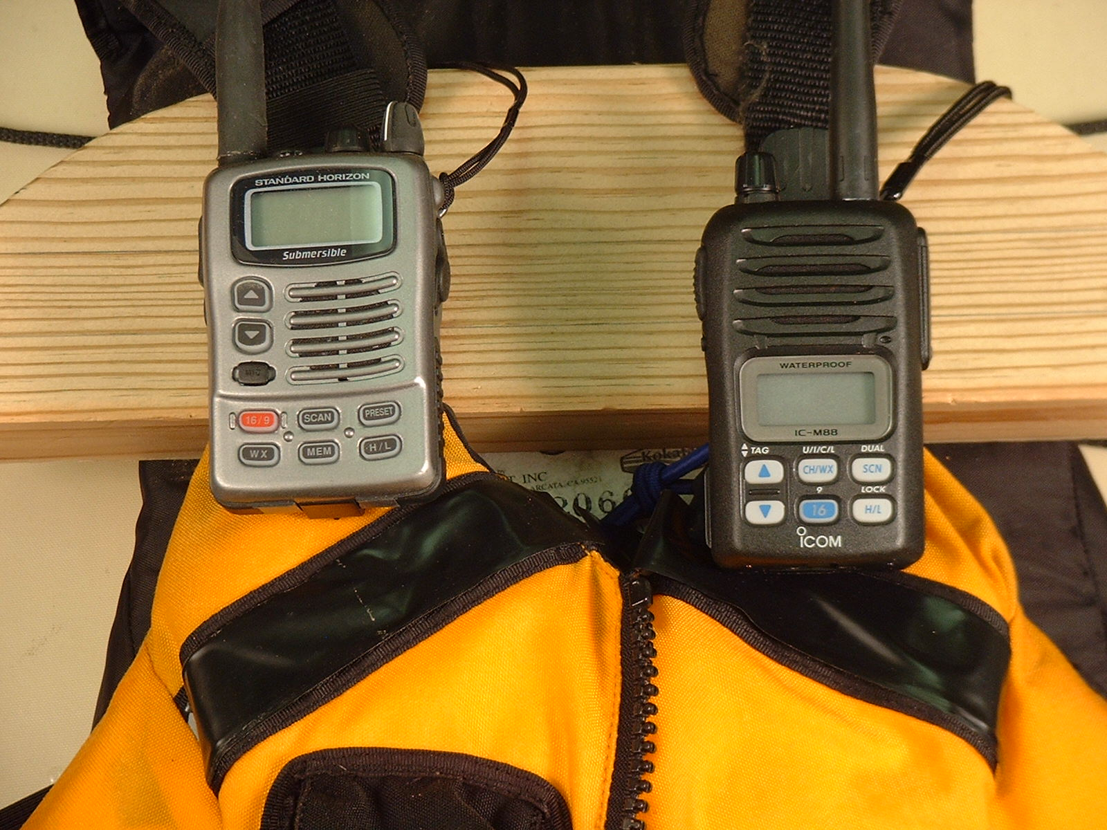 Two VHF radios mounted to shoulder straps with their antennas toward the outside.