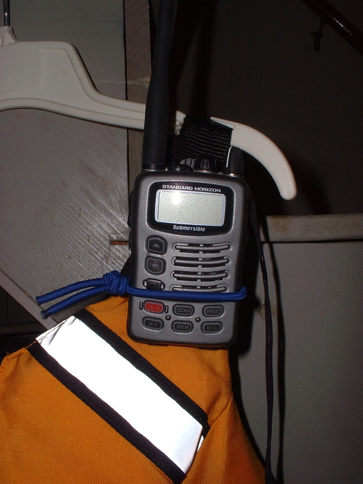 VHF radio in its mount on PFD shoulder strap